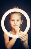Beautiful young girl gymnast holding a glowing circle and making quiet gesture Royalty Free Stock Photography