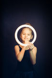 Beautiful young girl gymnast holding a glowing circle and making quiet gesture Stock Photo