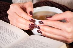 Woman hands with cup of tea and brown manicure on finger nails and open book on wooden retro desk. Beautiful young girl hands with cup of tea and brown manicure stock photos