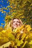 The beautiful young girl a happy woman smiling and holding a yellow maple leaves walking in autumn park Royalty Free Stock Photos