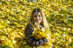 The beautiful young girl a happy woman smiling and holding a yellow maple leaves walking in autumn park Royalty Free Stock Images