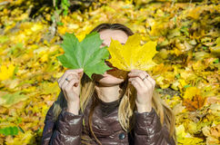 The beautiful young girl a happy woman smiling and holding a yellow maple leaves walking in autumn park Stock Images
