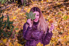 The beautiful young girl a happy woman smiling and holding a yellow maple leaves walking in autumn park Stock Photography