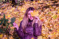 The beautiful young girl a happy woman smiling and holding a yellow maple leaves walking in autumn park Stock Photo