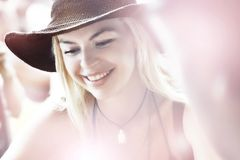 Beautiful young girl in a hat smiles in a cafe on a pink background. Selective focus. Soft focus Royalty Free Stock Image