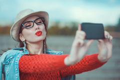 Beautiful young girl in the hat taking picture of herself, selfi Stock Image