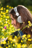 Beautiful young girl with headphones in the flowers Stock Photo