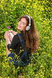 Beautiful young girl with headphones in the flowers Royalty Free Stock Photography