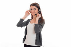 Beautiful young girl in headphones and gray jacket turned aside and keeps hands the microphone near the face Royalty Free Stock Photography