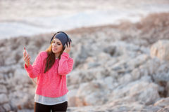 Beautiful young girl with headphones and mobile phone. Beautiful young girl with headphones and smart phone at the beach Royalty Free Stock Photos