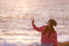 Beautiful young girl with headphones. And smartphone at the beach Stock Photography