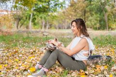 Beautiful young girl with her Yorkshire terrier dog puppy enjoying and playing in the autumn day in the park selective focus royalty free stock photo