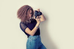 Beautiful young girl hipster makes the images, photographs on the camera in jeans and a black t-shirt in the Studio stock photography