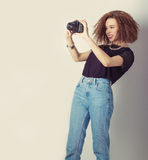 Beautiful young girl hipster makes the images, photographs on the camera in jeans and a black t-shirt in the Studio stock images