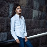Beautiful young girl hipster standing. Against the stone wall Stock Photography