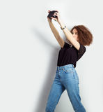 Beautiful young girl hipster takes photos, shoots selfe, taking pictures of himself on camera in jeans and a black t-shirt Stock Photo