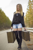 Beautiful young girl hitchhiking Stock Image