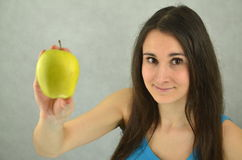Beautiful young girl is holding an apple Royalty Free Stock Image