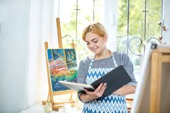 Pretty blode girl looking on a album and smiling. Art concept, stock images