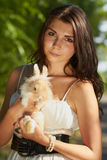 Beautiful young girl holding a bunny Stock Image