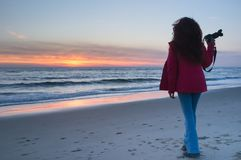 Beautiful young girl holding a camera and watching the sunset on the shore royalty free stock photography