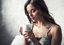 Girl in bed. Beautiful young girl is holding a cup of coffee/tea while resting at home Royalty Free Stock Photography