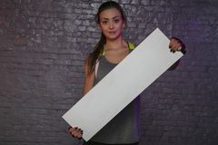 Beautiful young girl holding an empty board, copy space for advertising, muscles and gym, conceptual photo, advertising space stock photo