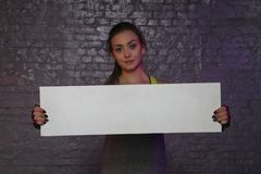 Beautiful young girl holding an empty board, copy space for advertising, muscles and gym, conceptual photo, advertising space stock photos