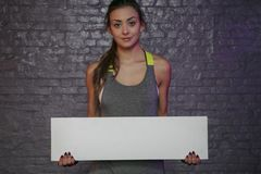 Beautiful young girl holding an empty board, copy space for advertising, muscles and gym, conceptual photo, advertising space stock photography