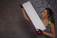 Beautiful young girl holding an empty board, copy space for advertising, muscles and gym, conceptual photo, advertising space royalty free stock photo