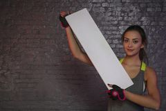 Beautiful young girl holding an empty board, copy space for advertising, muscles and gym, conceptual photo, advertising space royalty free stock photos