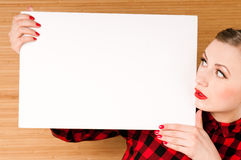 Beautiful young girl holding an empty white poster Royalty Free Stock Images