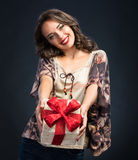 Beautiful young girl holding gift box on a dark background Stock Photo