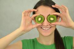 Beautiful young girl is holding kiwi fruit Stock Photography