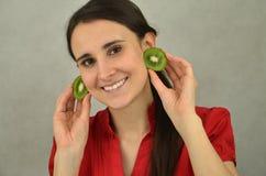 Beautiful young girl is holding kiwi fruit Royalty Free Stock Photo