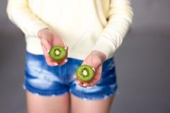 Beautiful young girl holding kiwi. Healthy food. Royalty Free Stock Image
