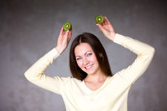 Beautiful young girl holding kiwi. Healthy food. Royalty Free Stock Images