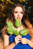 Beautiful young girl holding leaves in hands Stock Image