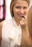Beautiful young girl holding lipstick. Stock Photo