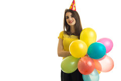 Beautiful young girl holding a lot of balloons with a cone on her head and smiling Royalty Free Stock Photography