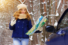 Beautiful young girl holding map and phone navigator, standing near car on the forest road, wearing blue jacket. Travel girl. Stock Photography
