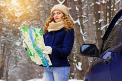 Beautiful young girl holding a map standing near a car on the road, wearing blue jacket. Travel girl. Stock Photos