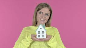 Beautiful young girl holding model house, pink background stock video footage