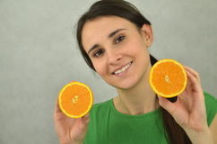 Beautiful young girl is holding an orange Royalty Free Stock Photography