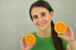 Beautiful young girl is holding an orange Royalty Free Stock Images