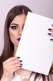 Beautiful young girl holding a paper over his face. Stock Photo