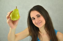 Beautiful young girl is holding a pear Stock Photo