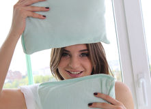 Beautiful young girl holding a pillows. studio. Beautiful young girl holding a pillows. She stands by the window . Her face between two pillows , she smiles Stock Photo