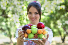 Beautiful young girl holding a plate with fruits. Selective focus on plate. Healthcare baby Stock Image