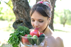 Beautiful young girl holding a plate with vegetables and enjoying the smell Stock Photography